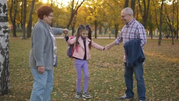 Grandparents are playing and having fun in autumn Park with her granddaughter.