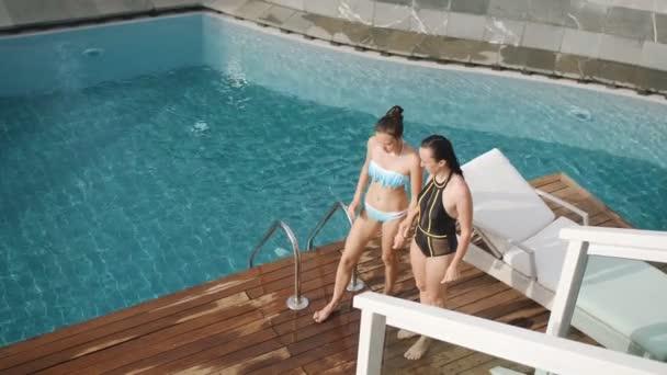 Mutter und Tochter springen gemeinsam in Schwimmbad. glückliche Familie genießt den Sommer spielerisch beim Plantschen im kühlen Nass.