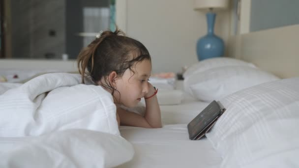 Little girl lying in bed under a blanket and watching cartoons on the tablet pc.