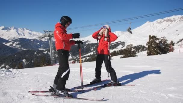 Muž lyžař na vrcholu hory čeká na své milované, která táhne se k němu na lyže.