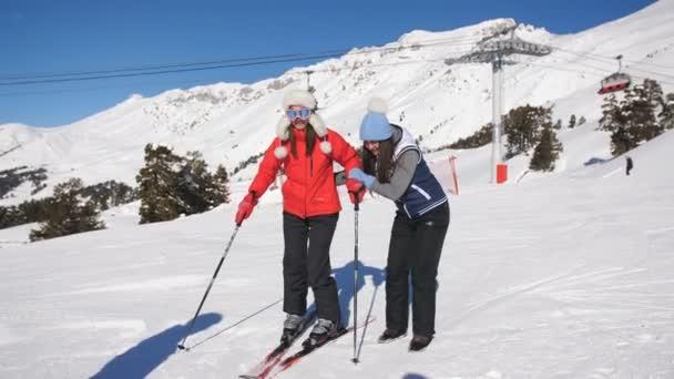 Dívka učí lyžovat kamarádku. Pomáhat jí stát na úbočí hory.