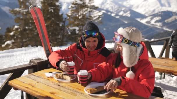 Pár lyžařů v horách, kde obědvá v restauraci.