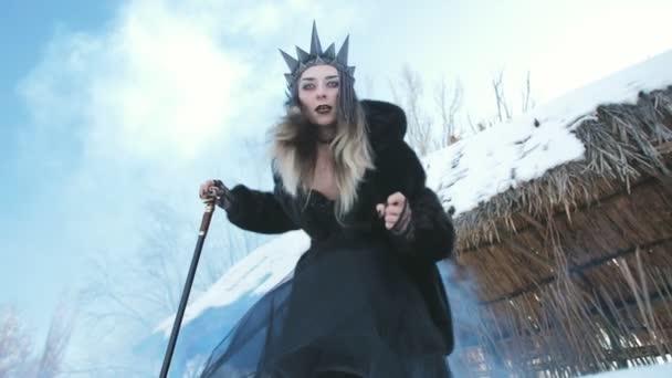 Sněhová královna v černém a s holí v rukou je zastrašující a dívá se do kamery.