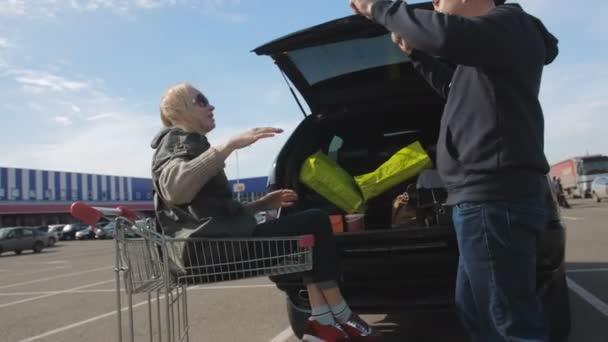 Šťastný pár se baví na parkovišti nákupního centra. Muž se válí v nákupním vozíku..
