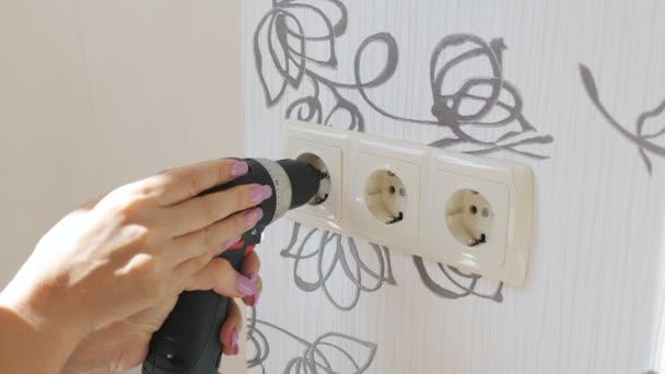 Detailní záběr ženských rukou se šroubovákem odšroubování zásuvky na zdi v bytě.