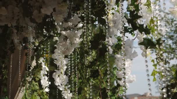 Decorated with flowers and chains wedding ceremony. Romantic decorations jewelry at the marriage.