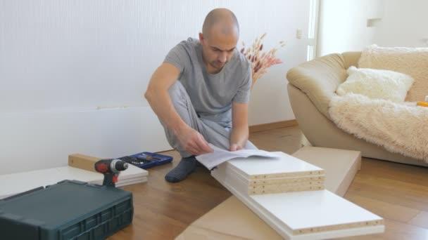 Ein Mann liest auf dem Boden sitzend die Anweisungen, bevor er mit der Montage der Möbel beginnt.