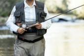 Fotografie Rybáře tyčinkou muškaření v krásné řeky