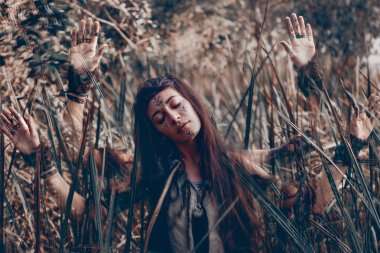 Beautiful young woman model with very long hair on branches. witch craft concept