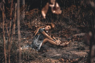 beautiful young boho style woman sitting on ground outdoors