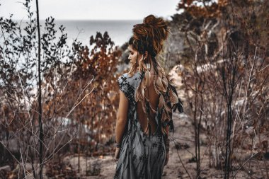 portrait of beautiful young woman through the dry branches