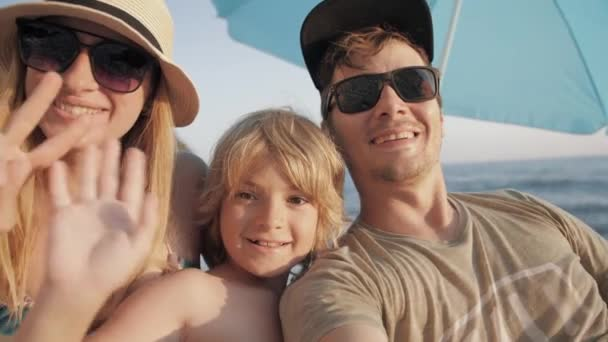 Smiling family of three in sunglasses taking selfie on beach