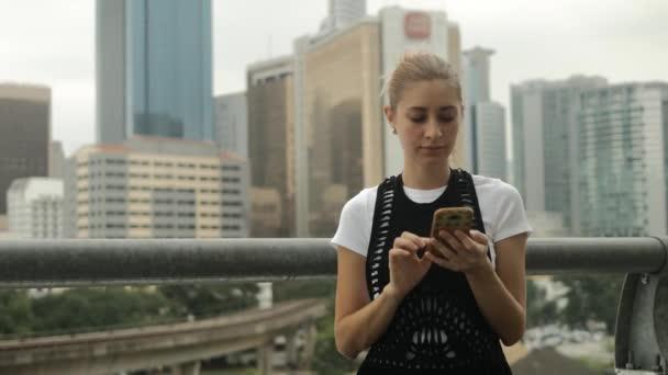Mladá dívka, která používá mobilní telefon venku na pozadí města.