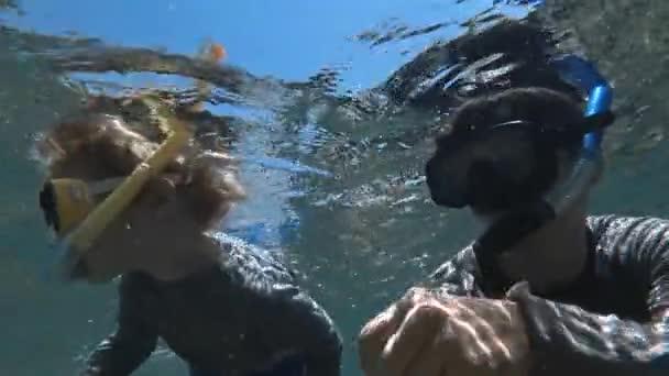 Snorkeling bambino immersioni con padre in acqua cristallina delloceano con pesci