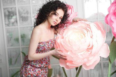 A beautiful slender brunette girl holds a huge peony flower from the paper.