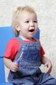 malé dítě sedí na židli se zubním kartáčkem v ruce