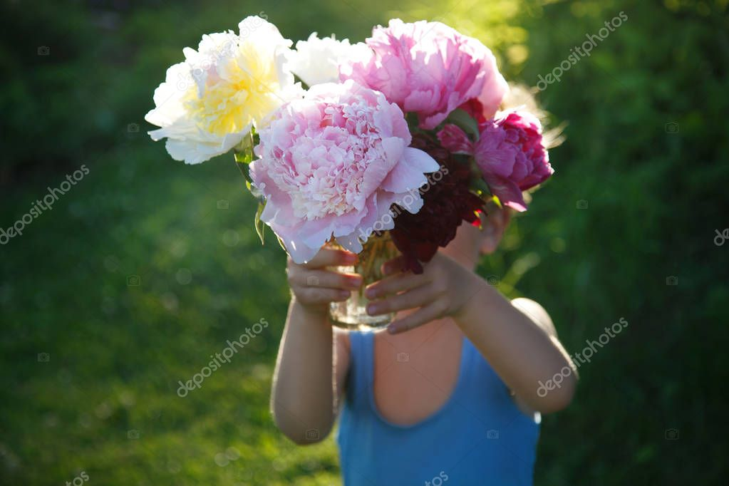 A cute baby is holding out a large bouquet of pink peonies in the open air.