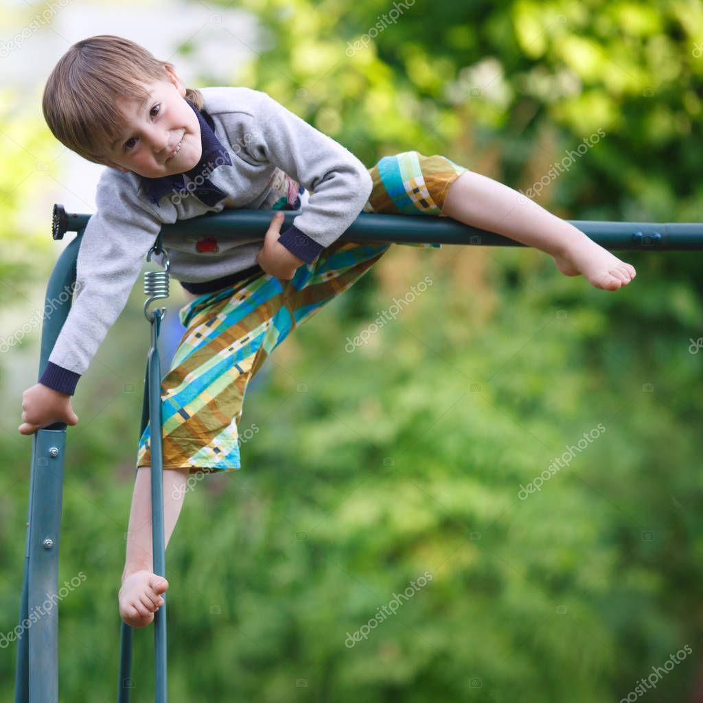 boy climbing on the playground summer day