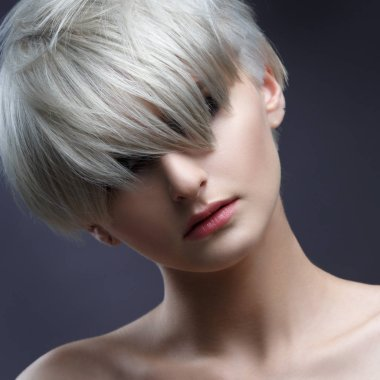 Portrait of blonde woman with stylish short haircut on gray background.