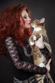Fotografia Fashion portrait of red-haired woman with spiders on face and striped cat in hands.