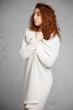Portrait of red-haired girl in a cardigan and body on gray background.