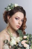 Portrét krásné nevěsty s kyticí na šedém pozadí