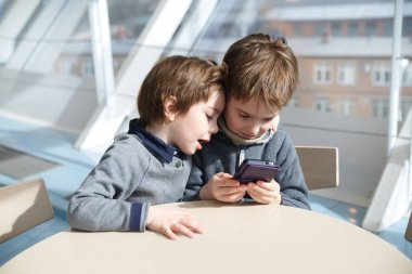 Two little boys play games on the phone.