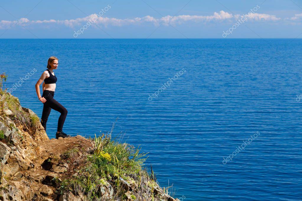 Young girl at a rocky seashore