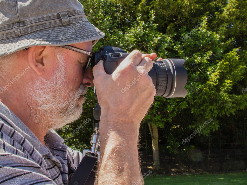 Elderly man take a picture of nature outdoor, hobby during a pension, free time, vacations.
