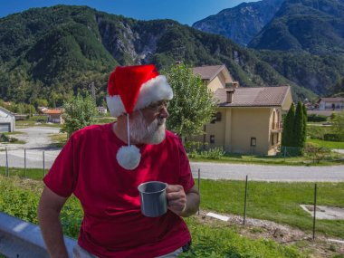 Tourist bearded senior man in red shirt and hat of Santa Claus drinking from large mug.