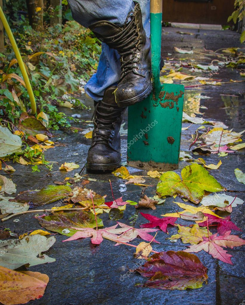 Old Reliable leather boots on the background of wet surface with  autumn leaves, close-up.