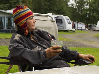 The pensioner is sitting with a plastic cup of fresh fruit and vegetable smoothi in a green forest near the tent. Life in a camp in nature,
