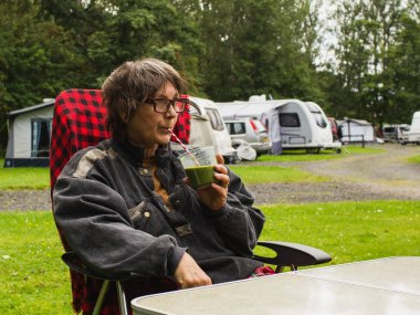 Woman 60-s drinking healthy  smoothi, enjoying outdoors lifestyle.