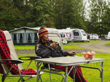 Woman 60-s with funny hat sitting in a campchair, drinking healthy  smoothi and enjoying outdoors lifestyle.