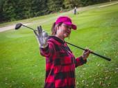 Aktivní dívka středního věku golfista na pozadí zeleného golfového co