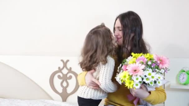 mother and daughter hugging each other. daughter is giving her mother a flower bouquet for mothers day