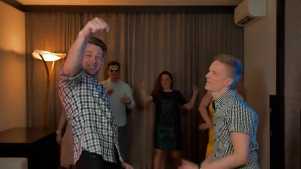 Two guys and their friends dancing at home party