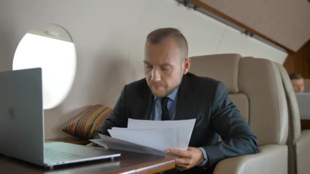 Businessman working with documents and laptop in private jet