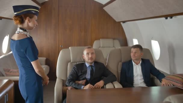 Business people, inside of private jet relaxing while flying and speaking with stewardess