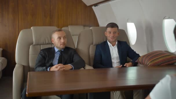Businesspeople discussing inside business private jet armchairs