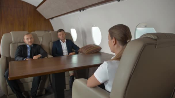 Two confident male entrepreneurs and successful female businesswoman inside first class jet