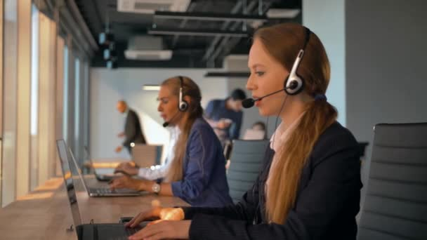 Female operator agent with headsets working in a call centre.