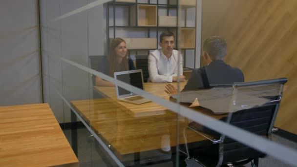 Businesspeople discuss the deal in modern office indoor evening