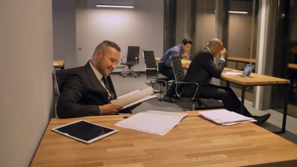 Confident boss entrepreneur with colleagues working with documents in night office