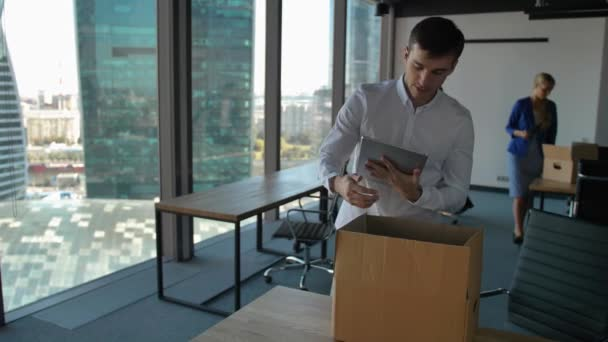 Young employee unpack box with docs and items. His colleagues walk near in modern office