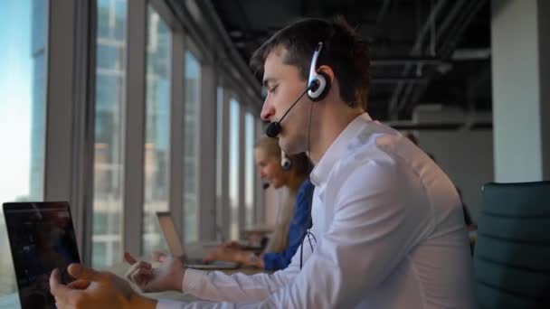 Handsome businessman entrepreneur in headset calling to cuctomers in business office call center