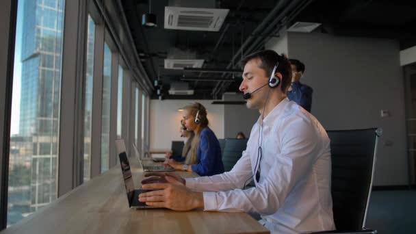 Call centrum zaměstnance v kanceláři rozhovoru s klientem a pak úsměv do kamery