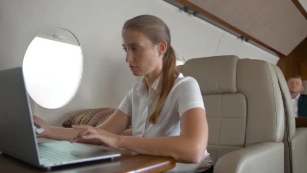 Portrét mladé ženy psaní na notebooku v kabině luxusní soukromé letadlo
