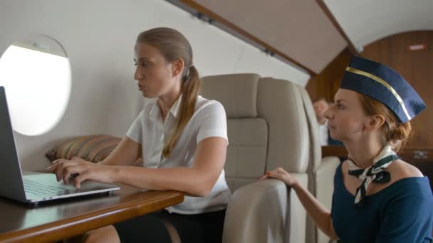 Air hostes asking businesswoman about service inside of luxury business plane