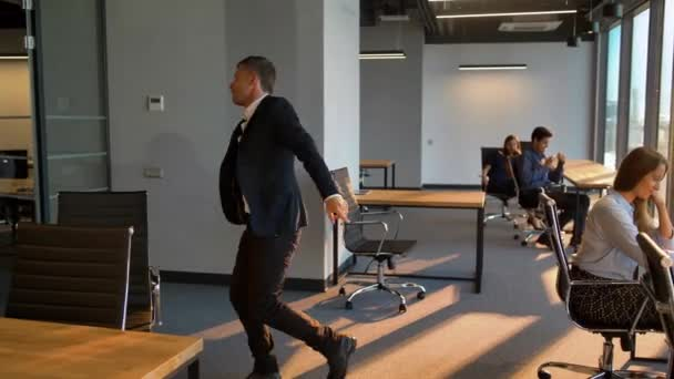 Businesspeople looking at dancing male colleague